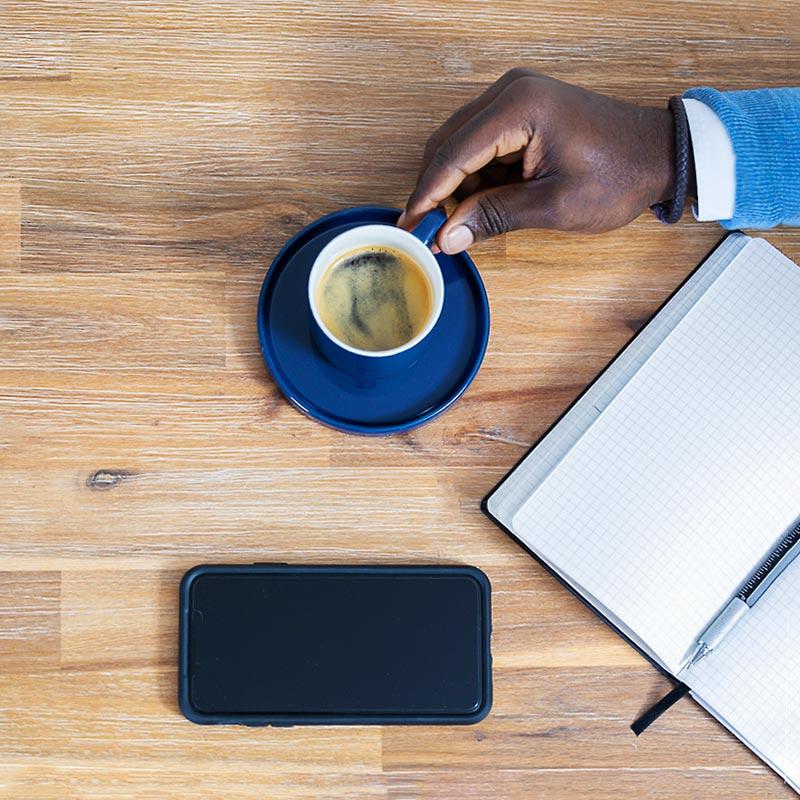 Hand an Kaffe Tasse, Handy und Schreib-block für Webdesign