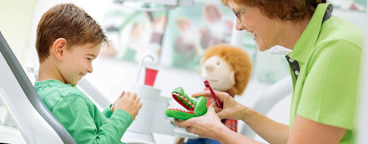 Frau zeigt Kind ein Spielzeugkrokodil. Shooting in einer Praxis in der Kölner Innenstadt.