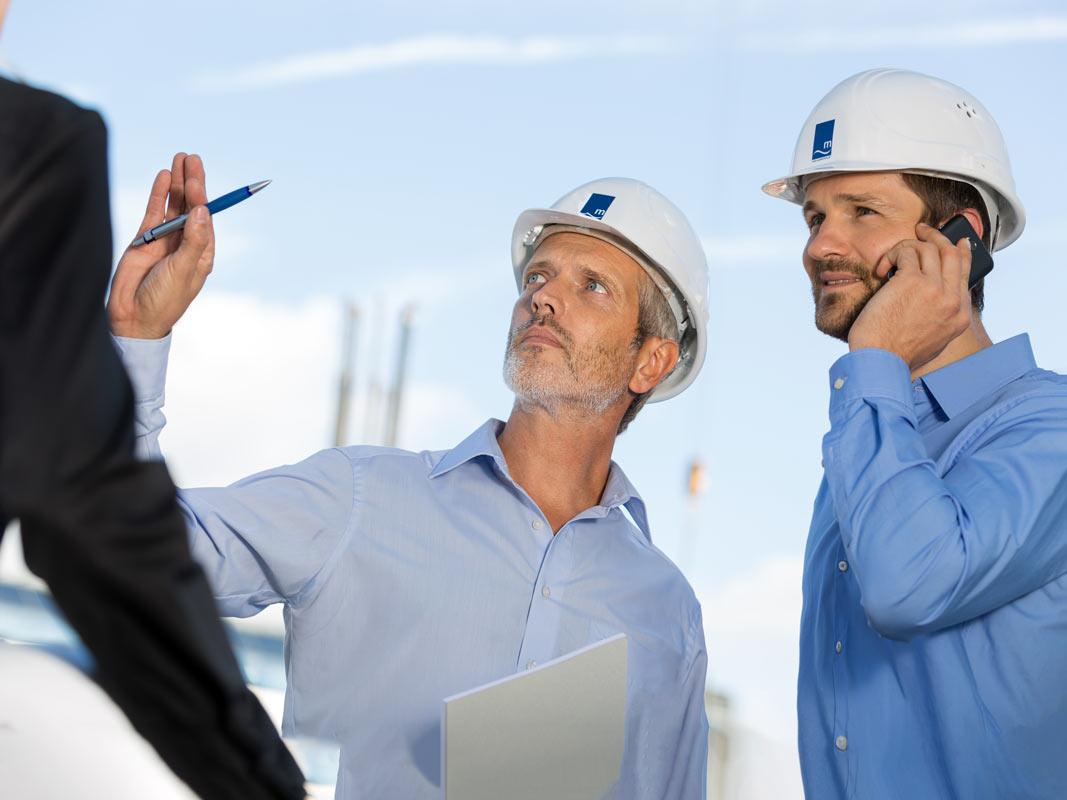 Bauarbeiter und Architekt im Gespräch auf der Baustelle in Köln.