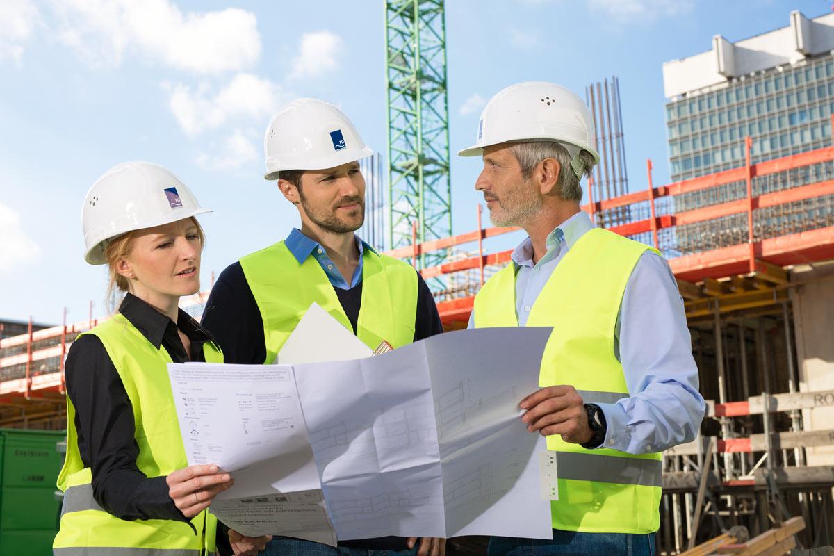 Bauarbeiter mit Bauplan auf der Baustelle Klinikum Köln.