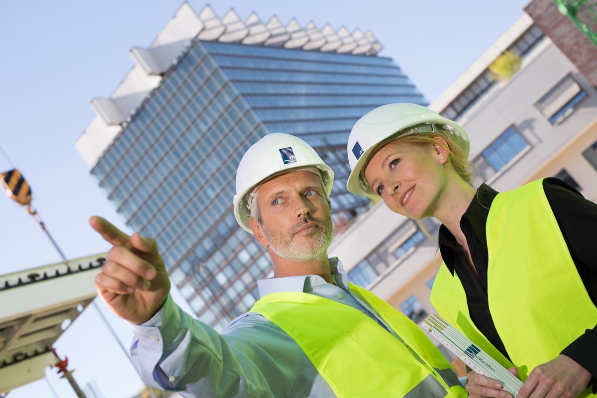 Mann und Frau mit Warnweste und Helm auf Baustelle in Köln.
