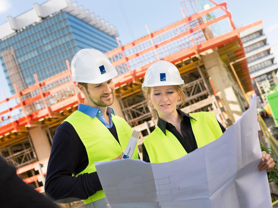 Ingenieure mit Bauplan auf der Baustelle der Uni Klinik Köln.