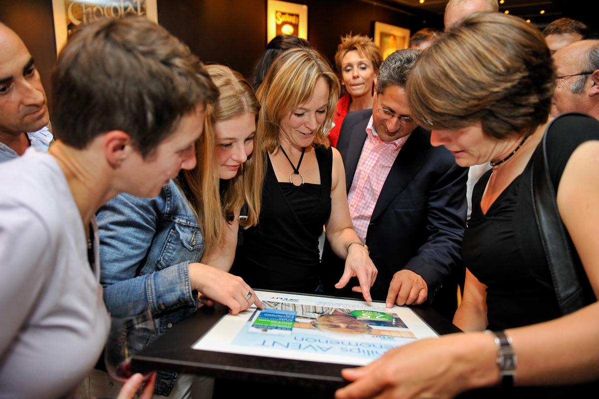 Gruppe spricht über eine Urkunde. Eventfoto aus dem Schokoladenmuseum in Köln.