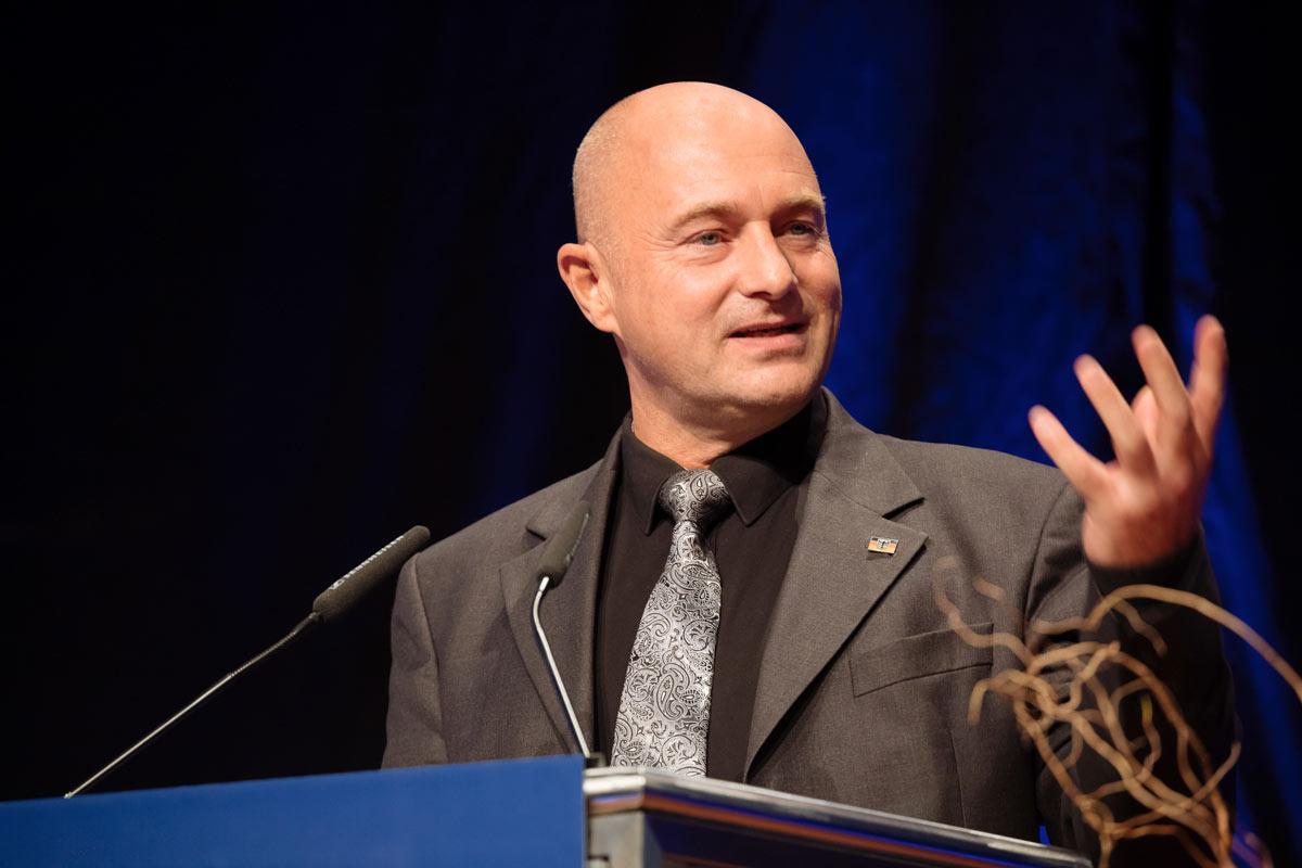 Mann im Anzug hebt die Hand bei seiner Rede, Kongress Forum Köln