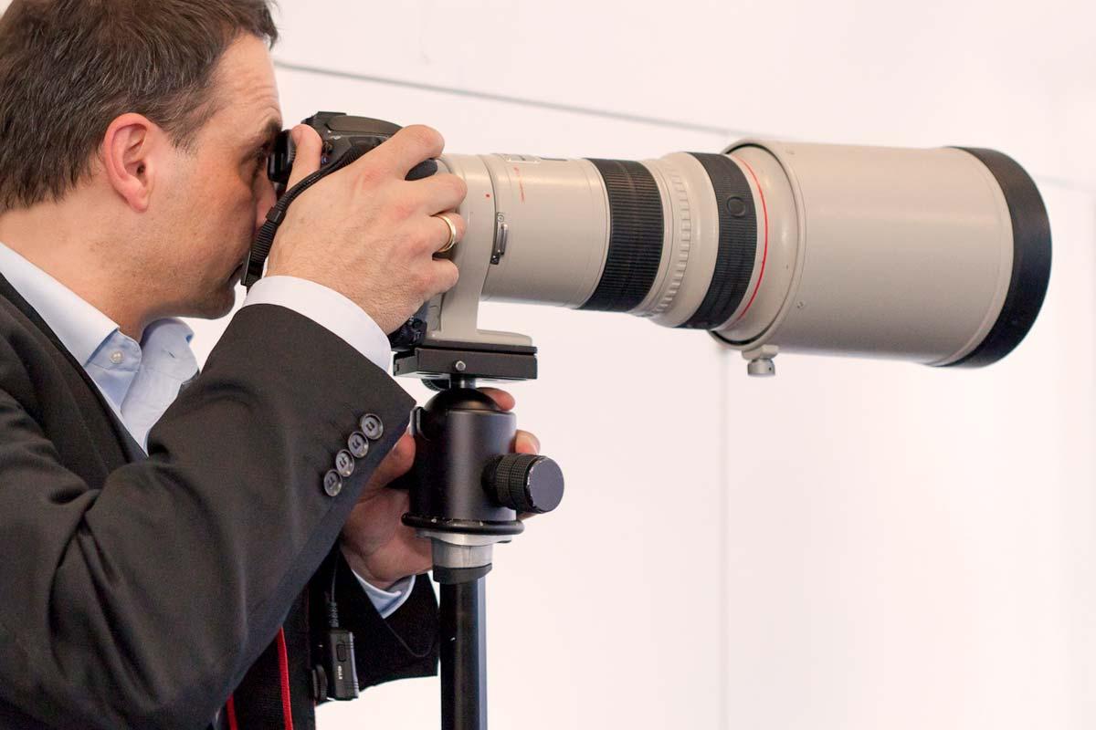Pressefotograf mit Kamera und Teleobjektiv