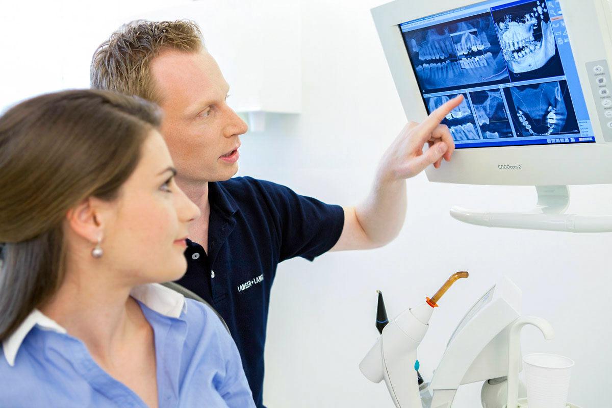 Zahnarzt und Patientin am Monitor Praxis Foto