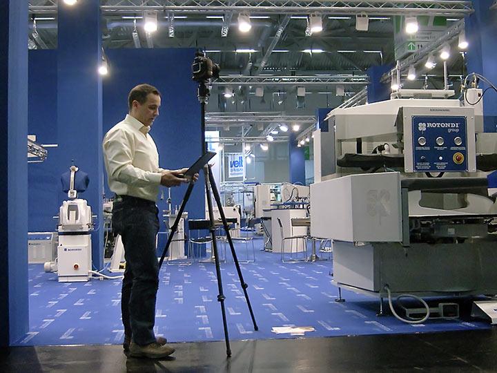 Messe Fotograf mit Kamera auf Stativ macht Messestand Foto